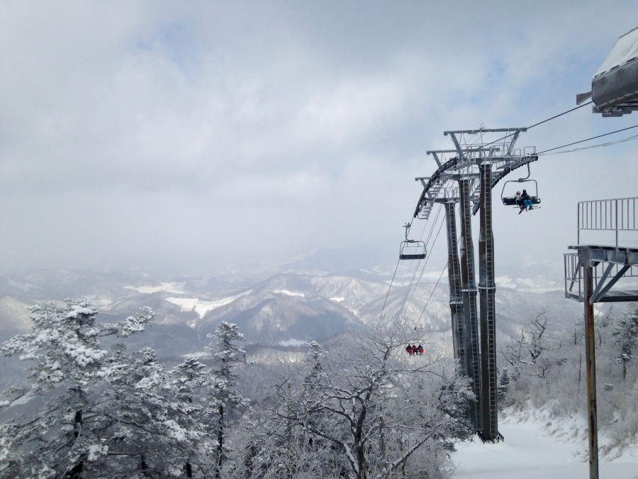 At the peak. Chairlift and mountains in the background.